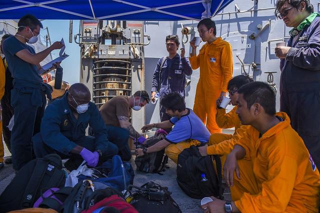 Sailors aboard USS Bainbridge (DDG 96) render aid to the crew of