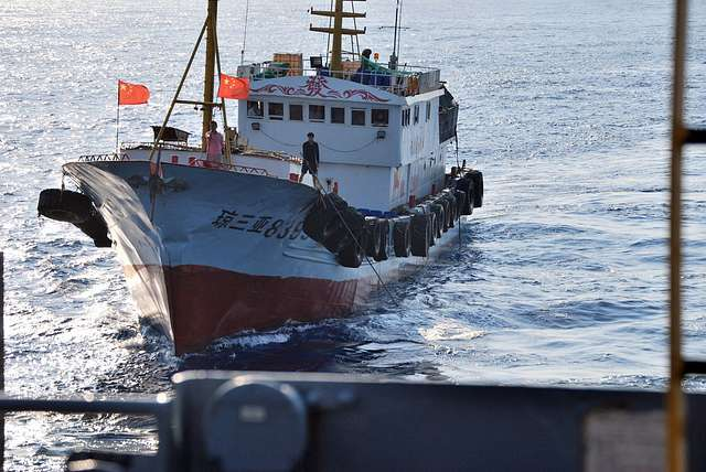 a-crewmember-on-a-chinese-trawler-uses-a-grapple-hook-in-an-apparent-attempt-d7042b